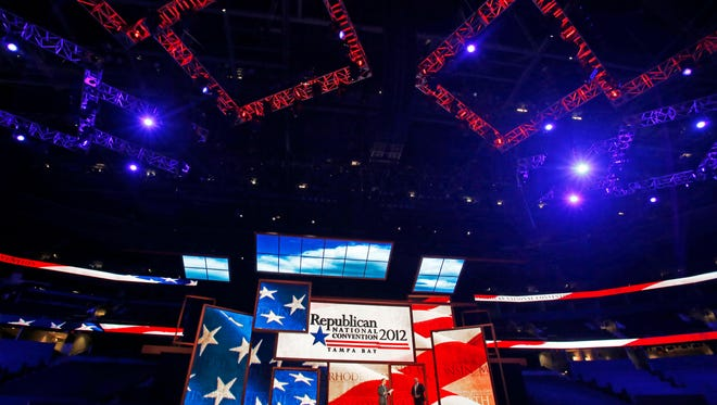 FILE - In this Monday, Aug. 20, 2012, file photo, Republican National Committee Chairman Reince Priebus, left, and convention CEO William Harris unveil the stage and podium for the 2012 Republican National Convention at the Tampa Bay Times Forum in Tampa, Fla. Trump has promised to liven up the 2016 Republican National Convention. But some of America's biggest corporations are bailing on the party. (AP Photo/Scott Iskowitz, File)