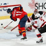 Florida Panthers' Jonathan Huberdeau (11) scores a goal past New Jersey Devils goaltender Cory Schneider (35) during the third period of an NHL hockey game, Saturday, April 11, 2015, in Sunrise, Fla. The Panthers defeated the Devils 3-2.