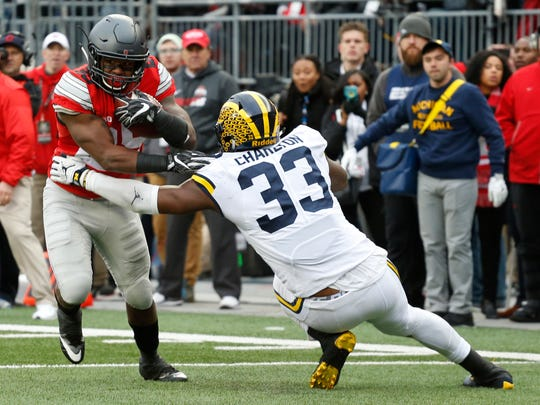 Ohio State running back Mike Weber (25) runs the ball as Michigan defensive end Taco Charlton (33) attempts to tackle him on Nov. 26, 2016, in Columbus, Ohio.