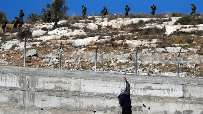 A Palestinian protester uses a slingshot to hurl stones towards Israeli security forces during clashes following a demonstration against the expropriation of Palestinian land by Israel in the village of Kfar Qaddum, near Nablus, in the occupied West Bank on Jan. 6, 2017.