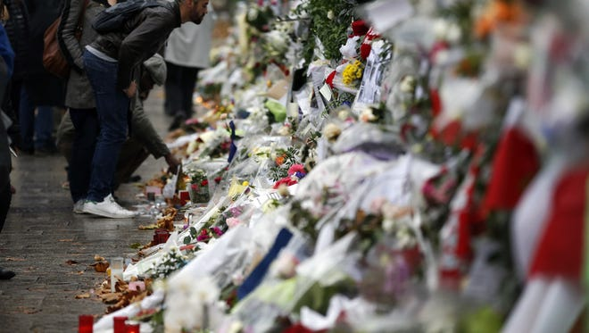 People look at flowers and card tributes placed outside the Bataclan concert hall in Paris, Thursday, Nov. 19, 2015, after last Friday's attacks.  The Belgian jihadi suspected of masterminding deadly attacks in Paris died during a police raid on a suburban apartment building, the city prosecutor's office announced Thursday, with France still reeling from the Friday attacks that killed 129 people and wounded hundreds of others.