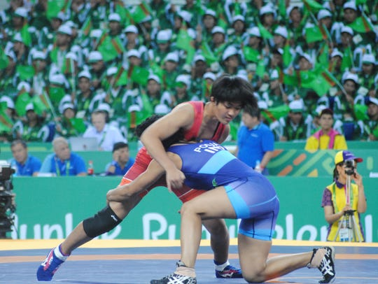 Rckaela Aquino, of Team Guam, in red uniform, battles