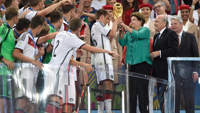 Brazil president Dilma Vana Rousseff (wearing green) and FIFA president Sepp Blatter (second from right) present the world cup trophy to Germany defender Philipp Lahm (16) after defeating Argentina and winning the 2014 World Cup at Maracana Stadium in July of 2014.