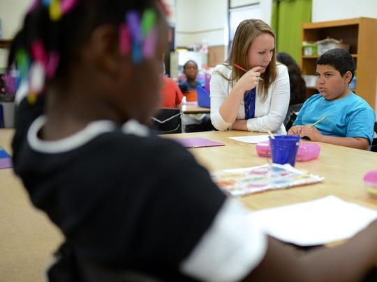 Megan Falish works with Dayshawn French on crafting a thank you card at Tank Elementary School in Green Bay.