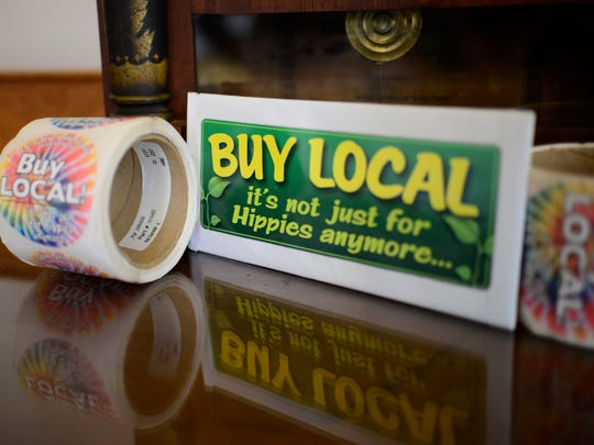 "Lt. Gov. Phil Scott shows off his unique ""buy local"" stickers that have been on his desk at the Statehouse for years."