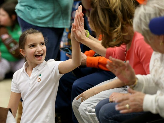 Rianne Maddaleno high-fives her family after her fourth
