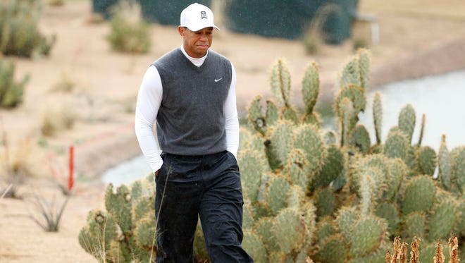 Tiger Woods walks off the 15th tee box after hitting his drive into the lake during the second round of the Waste Management Phoenix Open.
