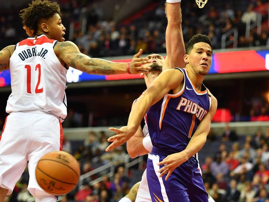 Phoenix Suns guard Devin Booker passes the ball past Washington Wizards forward Kelly Oubre Jr. during a Nov. 1 game at Capital One Arena in Washington D.C.