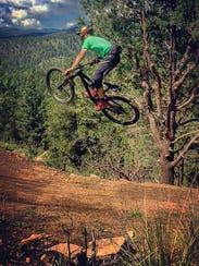 A mountain biker takes a jump on the Cedar Creek trail