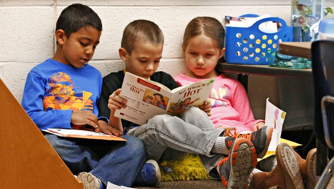 Baron Cottrell, Logan Woodward and Chloe Tranberg read in 2017 at Apache Elementary School in Peoria. The district is asking for funds to maintain all-day kindergarten programs.