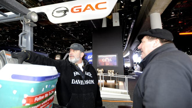 """Dock master CoCo Basile, left, with hi-lo driver Joe Karpinski, oversees the traffic mayhem behind the Detroit auto show at Cobo. """"Something has to be wrong with you,"""" says convention and shows exec Sam Tanari, """"to even take that job."""" Says Basile: """"I love it."""""""