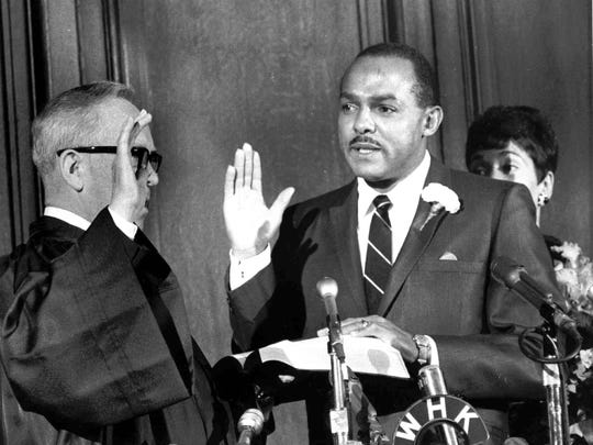 Carl B. Stokes is shown as he was sworn in as mayor of Cleveland on Nov. 13, 1967, by Municipal Judge Anthony A. Rutkowski as his wife Shirley watches.