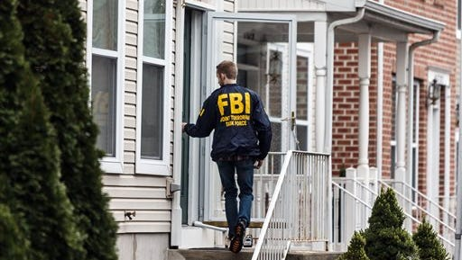 An FBI Joint Terrorism Task Force member enters a home in Harrisburg on Thursday where Jalil Ibn Ameer Aziz, 19, was arrested on charges he attempted to provide support to the Islamic State group.