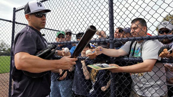 New York Yankees' Jacoby Ellsbury looks at a bat while signing autographs before a spring training baseball game against the Philadelphia Phillies Thursday, March 3, 2016, in Tampa, Fla.
