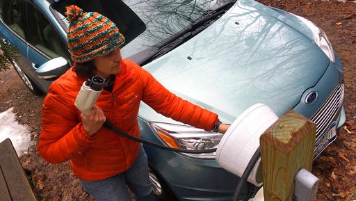 """In this Thursday, April 6, 2017 photo, Sunita Halasz shows how she charges her electric car at her home in Saranac Lake, N.Y. Halasz has tips for """"driving electric"""" along the lonely New York Adirondack Mountains roads: learn where the charging stations are, bring food and books for the kids during three-hour recharges, use the defroster in 10-second bursts since it sucks battery life, and have a backup plan."""