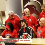 Surrounded by his parents and coaches, Nixa outfielder Patrick Hoerning (seated, center) signed a national letter of intent to play baseball for Drury University.