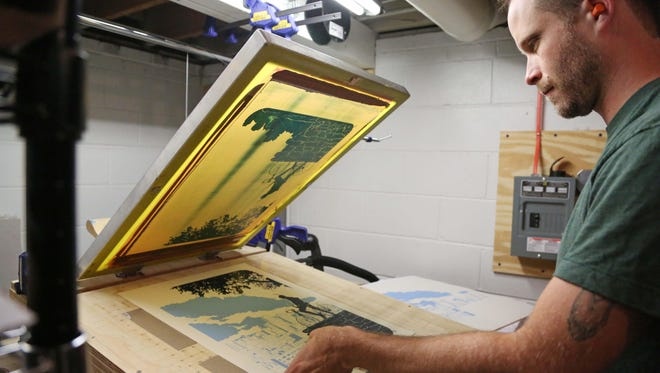 John Bosley, a graphic designer and print maker from Des Moines, works on a screen printer in the basement of his home, which he has converted to a print making studio, on Thursday, July 9, 2015. Bosley was the head designer for T-shirt shop Raygun but left to focus on his own designs.