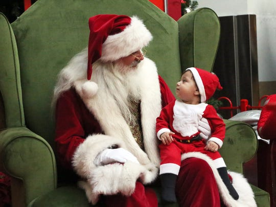 A baby glances at Santa Claus while posing for a picture with him during a busy shopping day at Bassett Place.
