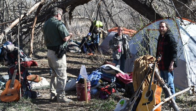 Law enforcement evict an encampment of the homeless in March. A community meeting to address concerns with the transient and homeless populations, such as harassment and feeling intimidated, will be held 6:30 p.m. Wednesday at Old Town Library.