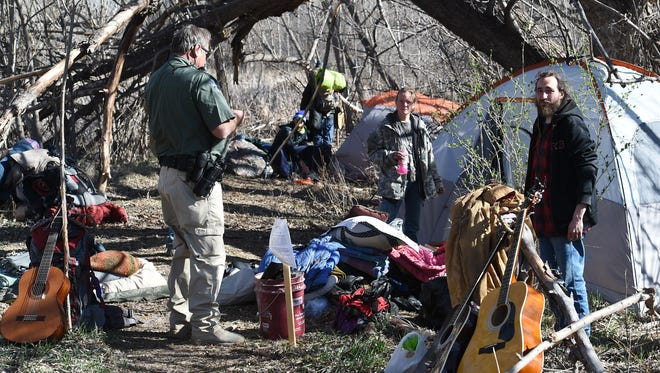 Law enforcement evict a homeless encampment in March. Gov. John Hickenlooper's budget calls for money for hundreds of housing units to address homelessness.