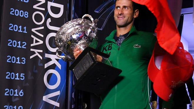 Serbia's Novak Djokovic carries the Norman Brookes Challenge Cup onto Margaret Court Arena to celebrate with fans after defeating Austria's Dominic Thiem in the men's singles final of the Australian Open tennis championship in Melbourne, Australia, early Monday, Feb. 3, 2020.