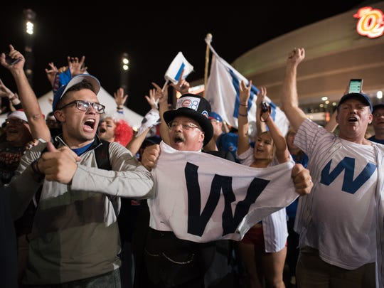 Cubs fans celebrate after the Chicago Cubs defeat the Cleveland Indians in game 7 of the World Series in the early morning hours on November 3, 2016 in Cleveland, Ohio. The Cubs defeated the Indians 8-7 in 10 innings to win their first World Series championship in 108 years.