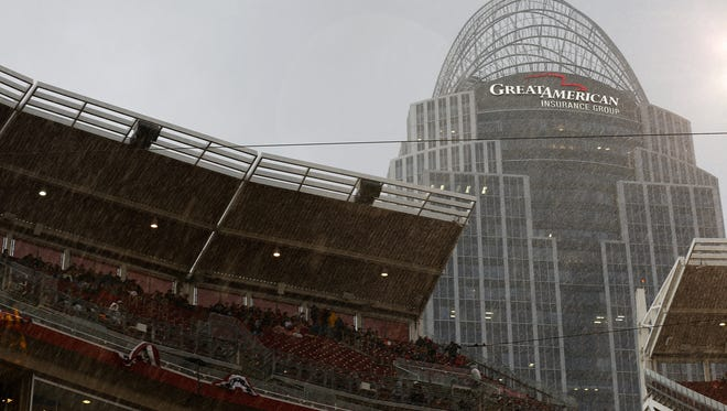 Fans take shelter as heavy rain turns to sleet before the first inning of the MLB game between the Cincinnati Reds and the Pittsburgh Pirates at Great American Ball Park on Friday, April 8, 2016. After three innings the Reds led 3-1.