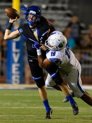 Chandler's Jacob Conover (#17) gets sacked by IMG Academy's Xavier Thomas (#19) in the second quarter of their high school football game on Saturday, Aug. 26, 2017, at Chandler High School in Chandler, Ariz.