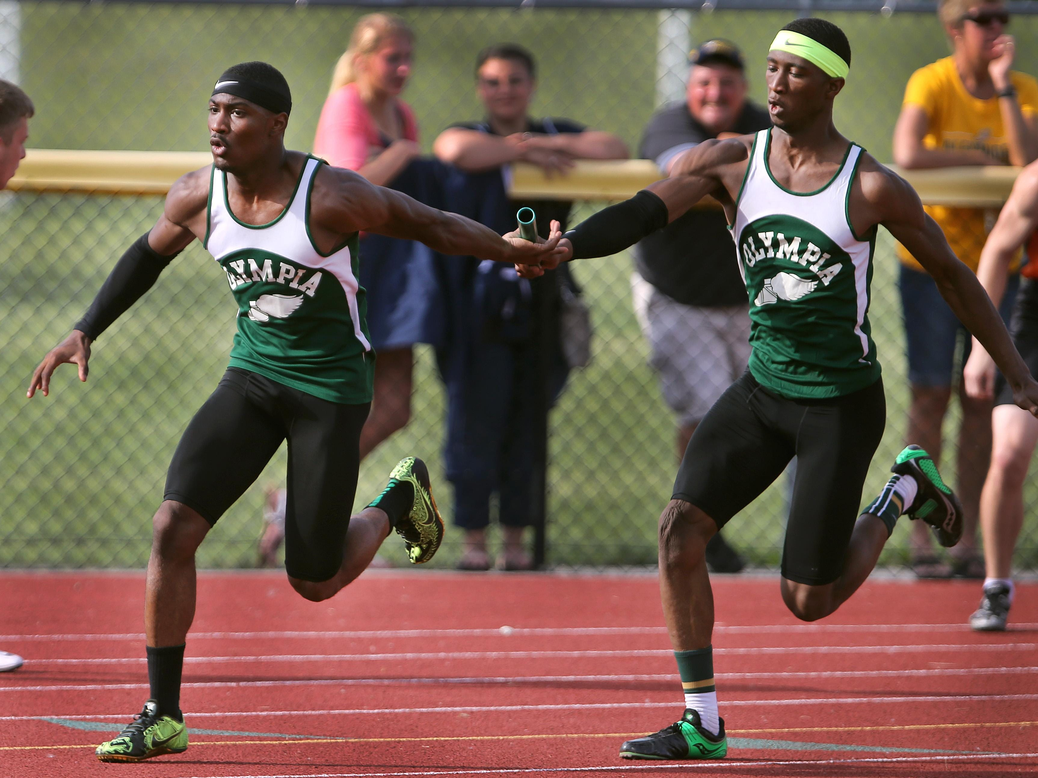 Olympia's Tre'Maine Moore, right, hands off the baton to anchor runner Carnell Noble enroute to winning the 4x100 relay at the state qualifier Friday at Caledonia-Mumford High School.