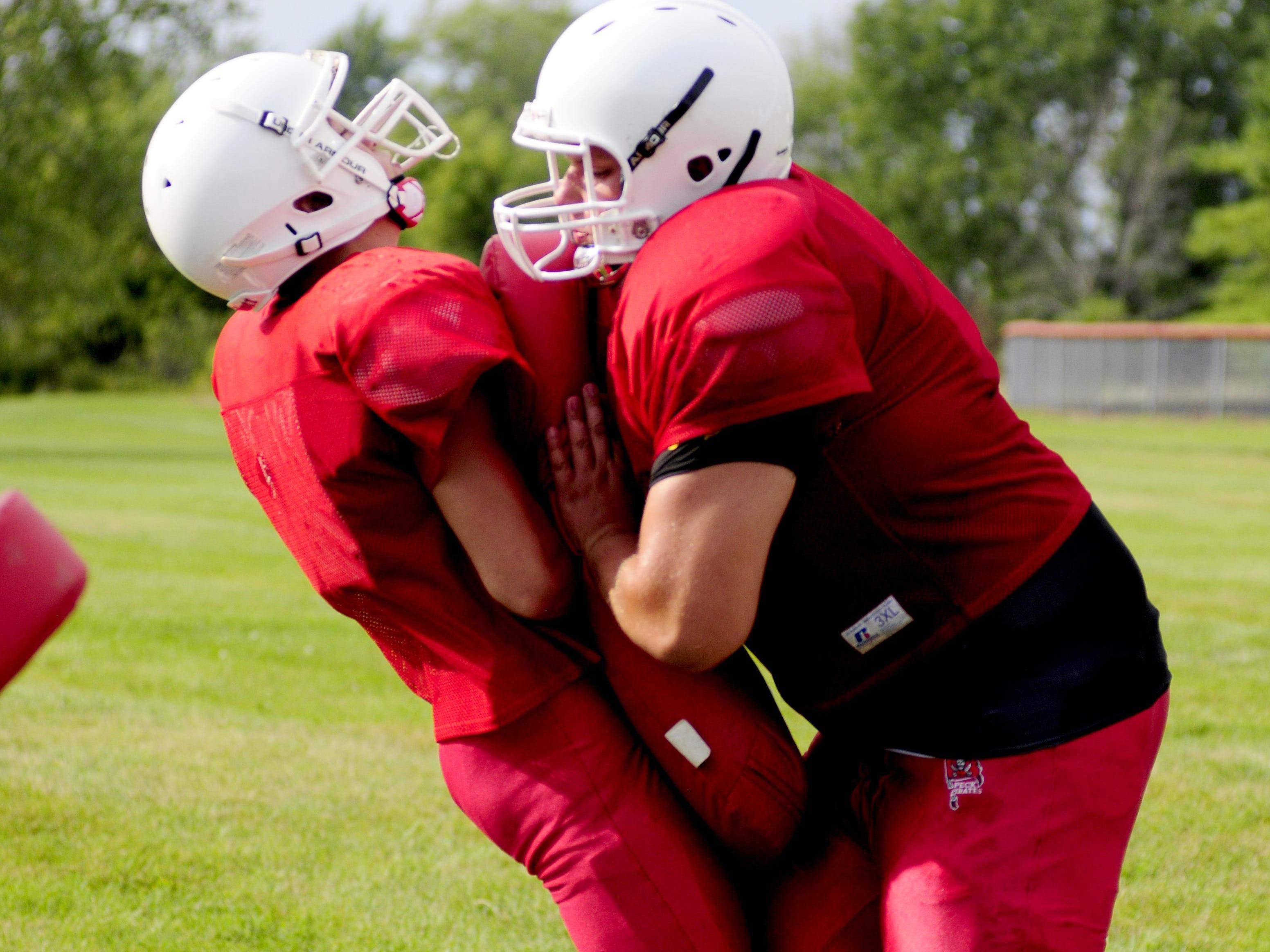 Peck's Noah Cubitt (right) goes through a drill at football practice.