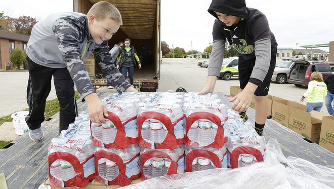 Garret and Isaac Glewen help unload a pallet of bottled water donated by Drexel Building Supply to the Wisconsin Supports North Carolina / Hurricane Matthew Relief fund in Lomira during Make a Difference Day 2016.