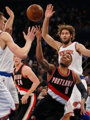 Portland Trail Blazers guard Damian Lillard (0) loses the ball as New York Knicks forward Kristaps Porzingis, left, and center Robin Lopez, right rear, defend during the first half of an NBA basketball game at Madison Square Garden in New York, Tuesday, March 1, 2016.