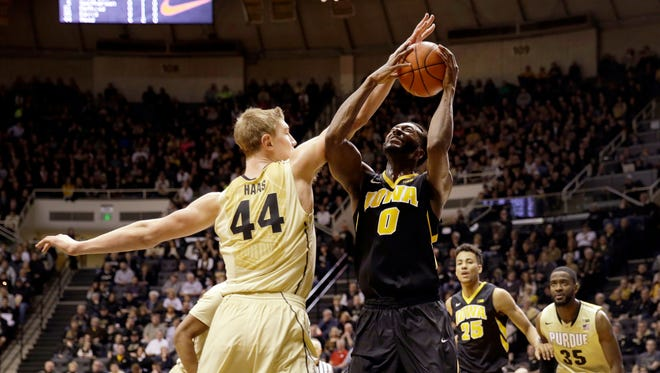 Iowa center Gabriel Olaseni (0) trys to shoot as Purdue center Isaac Haas (44) defends in the first half of an NCAA college basketball game in West Lafayette, Ind., Saturday, Jan. 24, 2015. (AP Photo/AJ Mast)