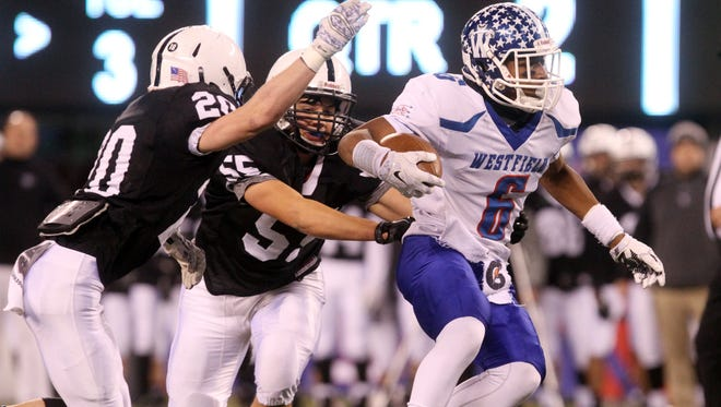Westfield's Jelani Pierre tries to shake Bridgewater-Raritan defenders Nick Mitchell (55) and John Kaye (20) in the North 2 Group V championship game, Thursday, December 3, 2015, at MetLife Stadium in East Rutherford.