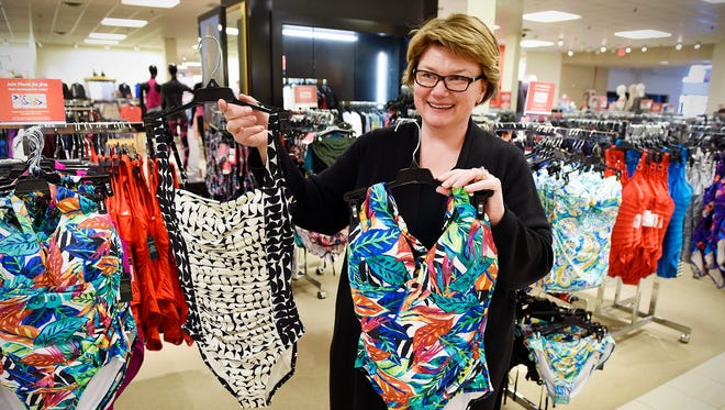Macy's manager Nancy Dorle show some of the popular swimsuit styles this season Friday, Feb. 10, including ruching, left,  and bright colors and patterns.