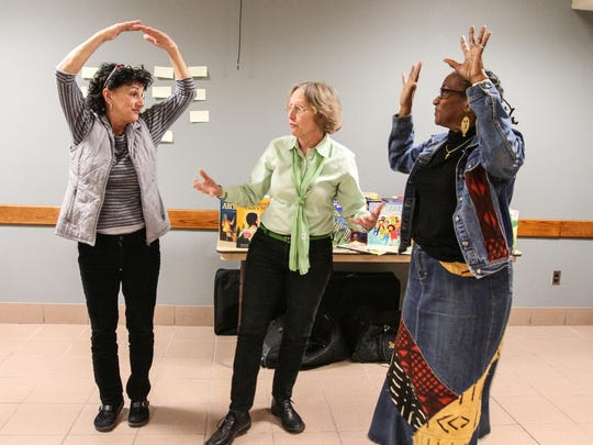 Storyteller Kathryn Widener, center, demonstrates how to create movement in a story with the help of Mary Ana Paterniti, on left, playing the moon, and Shirley Johnson, as the sun, during the Festival of Storytelling & World Music at The County College of Morris.
