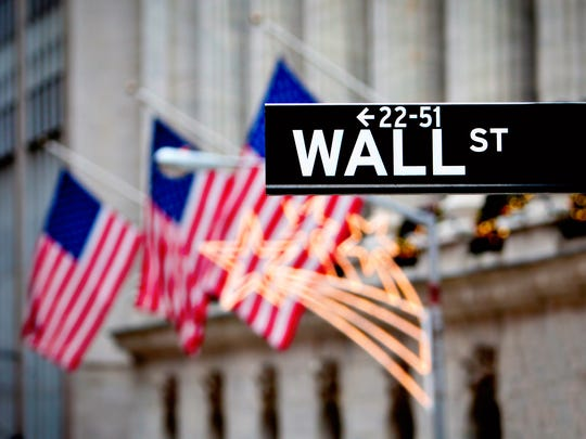 Wall Street street sign with three American flags in the background.