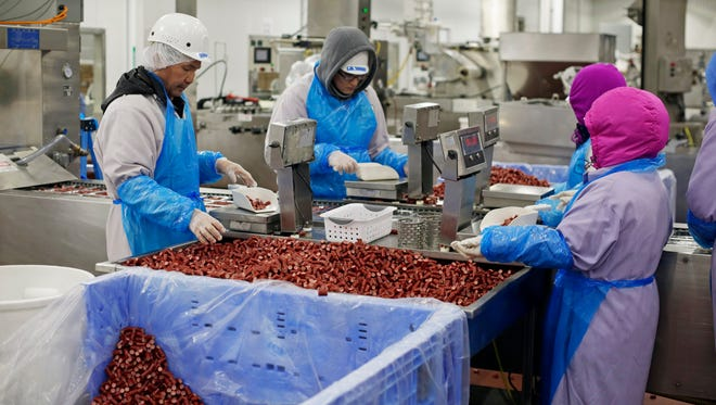 Old Wisconsin Sausage crews work on weighing bite sized snacks for a special order from a customer Wednesday January 25, 2017 in Sheboygan.