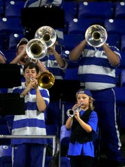 Ten-year-old Eli Deml plays his toy trumpet with the