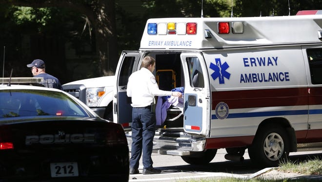 An Erway Ambulance responder closes the ambulance doors to transport a female after her vehicle collided with a silver Honda at Euclid Avenue and Clinton Streets in Elmira Tuesday morning.