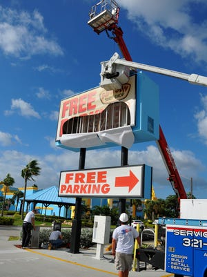 The deadline is approaching for businesses in Cocoa Beach to have their signs meet the new lower height requirements.  On Monday, workers from Art Kraft Signs and Dixon Electric were working  to lower the signs in the Ron Jons parking lot.