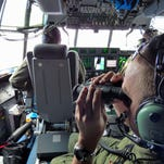 In this image released by the U.S. Coast Guard, Petty Officer 1st Class Mike Crosby, right, scans the surface of the Atlantic Ocean through his binoculars while in the cockpit of a Coast Guard HC-130J on July 28, 2015, while searching for Florida teens Perry Cohen and Austin Stephanos.