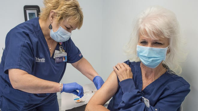 Nurse Phyllis Hallman, left, gives a booster shot of the Measles Mumps and Rubella vaccine to Elaine Burns Monday morning August 17, 2020 in Augusta, Ga.