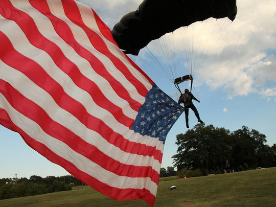 Parachutist Ron Alley lands outside the Civic Center of Anderson with his giant American flag as part of Celebrate Anderson.