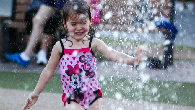 Ali Rios hesitantly plays in the Leapin' Lagoon splash pad during Prowl & Play at the Phoenix Zoo.