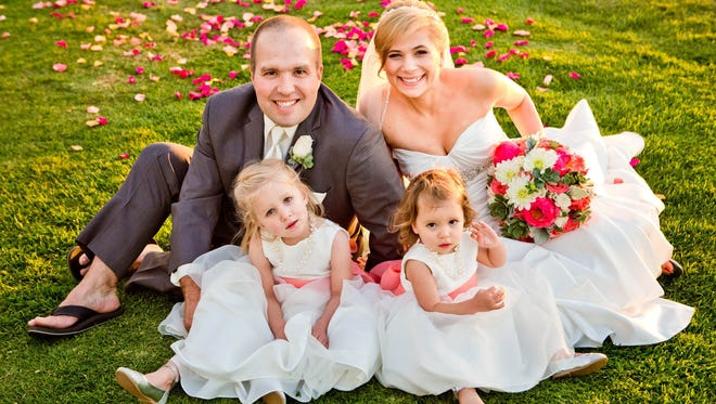 Jared and Sheila Elliott pose with their daughters Lexi, 3, left and Malia, 2 on their wedding day in November 2013. The couple, from Prior Lake, Minn., moved in with each other just before their first child was born, bought a house and decided to wait on having a wedding until they could save for the wedding they envisioned for themselves.