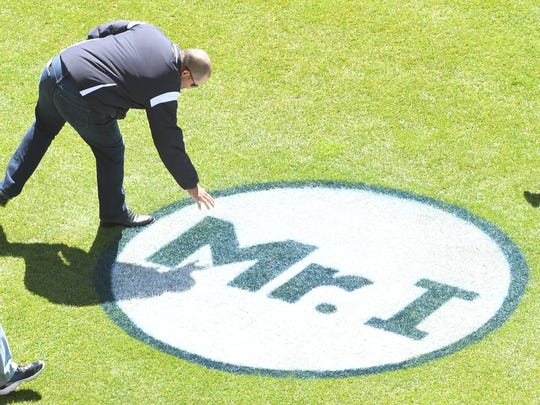 """On his way to the pitching mound to throw out the ceremonial first pitch, former Tigers catcher Pudge Rodriguez leans over and touches the """"Mr. I"""" logo on the field to commemorate late Tigers owner Mike Ilitch."""