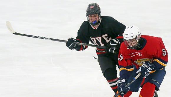 Pelham's Nate Rosenberg (5) tries to keep the puck