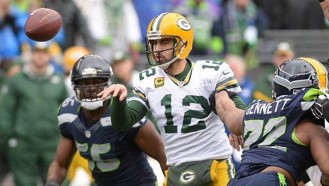 Green Bay Packers quarterback Aaron Rodgers flips a short pass that would fall incomplete under heay pressure against the Seattle Seahawks at CenturyLink FIeld in Seattle January 18, 2015.
