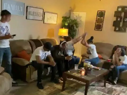 In this still image from video provided by the NFL, AJ Terrell, seated wearing headphones, listens while others celebrate during the NFL football draft Thursday, April 23, 2020, in Atlanta. Terrell was selected by the Atlanta Falcons during the first round. (NFL via AP)